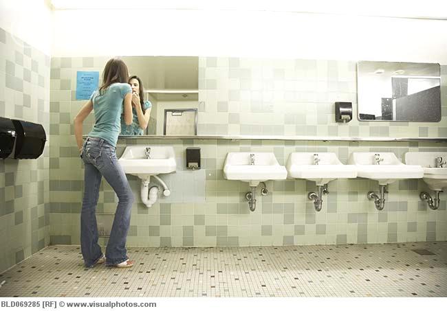 teenaged_girl_using_mirror_in_school_bathroom_bld0692854
